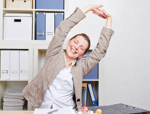 Ältere Frau mit Rückenschmerzen macht Dehnübungen im Büro